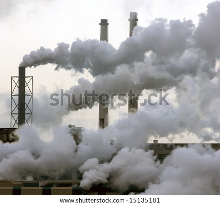A heavy industry production plant with steam and fumes from various exhausts