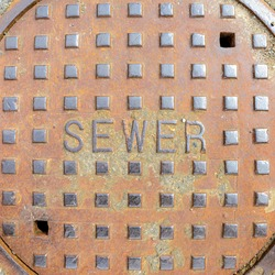 A heavy metal manhole cover with the word SEWER on it. Raised letters and square bumps. Light surface rust. Closeup view from directly above.