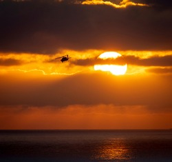 A helicopter banking left away from the sun during a cloudy sunset over the pacific ocean