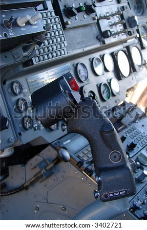 A helicopter cockpit with the control stick in the foreground and the instruments and switches in the background.