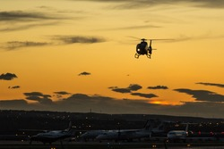 A helicopter coming in to land at sunset