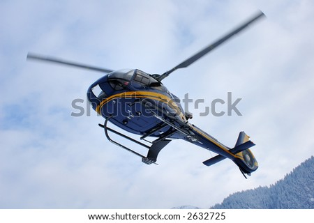 A helicopter coming in to land in the snowy mountains. Motion blur on the blades.