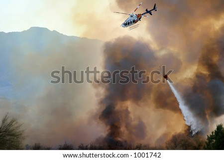 A helicopter dropping water on a fire. - stock photo