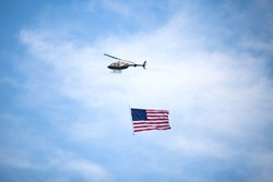 A helicopter flies over carrying an American flag