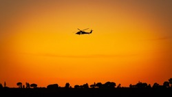 A helicopter flying in southern California against the setting sun.