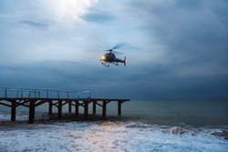 A helicopter is taking off during a sea storm.