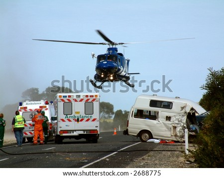 A helicopter lifts off, with patient on board at road crash scene
