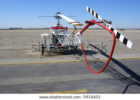 A helicopter used for crop spraying is parked on the ramp