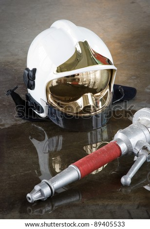A helmet and a nozzle on the floor in a fire station used by firefighters