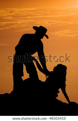 A hero of a cowboy helping up his girl after falling, with a beautiful orange sunset behind them.