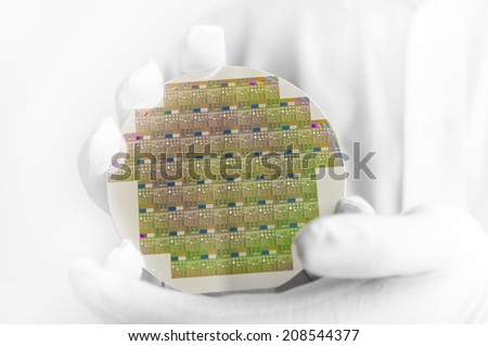 A hi-tech industry engineer in white gloves holding a silicon wafer inside a clean room lab.