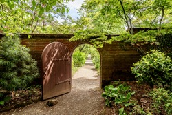A hidden gate is opening up to a beautiful English style garden with rounded hedges, beautiful flowers, & symmetric type design, with sand & brick sidewalks and footpaths to enjoy the scenic view.