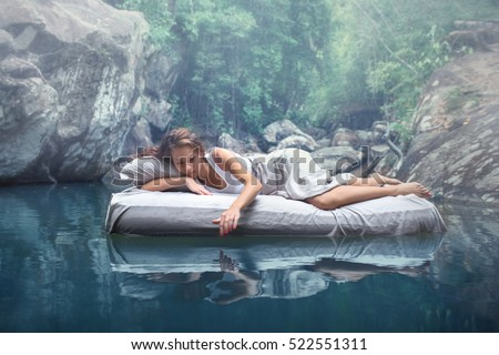 A hidden place. Sleeping woman in deep forest lies on airbed