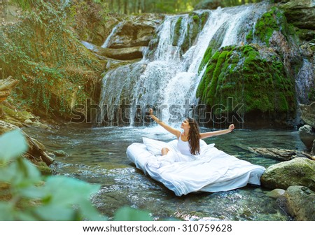 A hidden place. Sleeping woman in deep forest lies on airbed. Waterfall on back
