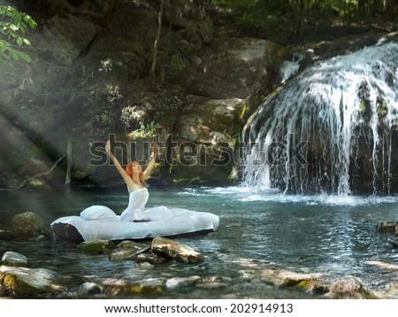 A hidden place. Sleeping woman in deep forest lies on matrace. waterfall on back Stock fotó ©