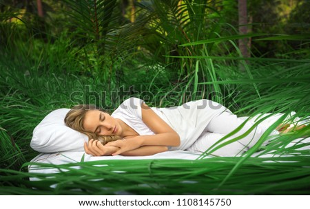 A hidden place. Sleeping woman in deep jungle forest lies on airbed