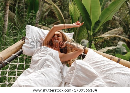 A hidden place. Sleeping woman in deep jungle forest lies on hammock with nature view, morning in the jungle on tropical island Bali Foto stock ©