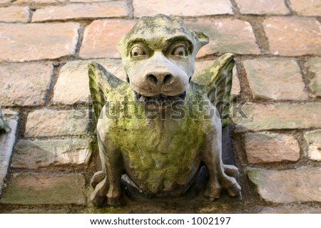 A hideous gargoyle stares down from an old roof in York, England.
