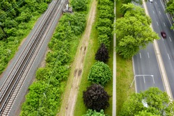 A high angle, drone view over a dirt road which is parallel to railroad tracks. Beside the dirt road, there is a treelined walking path and besides that, there is a highway.