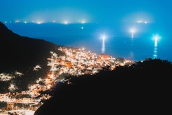 A high angle shot of a beautiful cityscape and landscape near the sea with a lot of illuminated buildings at night in Jiufen, Taiwan