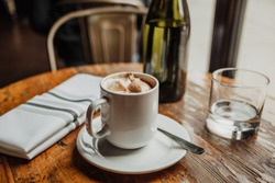 A high angle shot of a cup of cappuccino near a glass cup and a water bottle on a wooden table