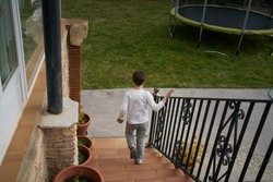 A high angle shot of a little boy going downstairs to play outside