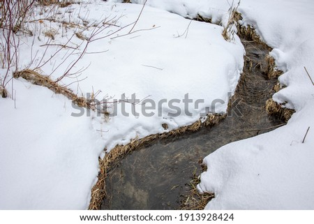 A high angle shot of a small dry river in a field covered in the snow in winter in Ontario, Canad Foto stock ©