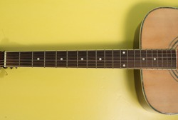 A high angle shot of  an acoustic guitar neck, fretboard or fingerboard isolated on yellow background. Strings, frets, surface are close-up shot that can be used for music training purpose.