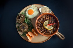 A high angle view/full length/color image of Egyptian, Arabian, Middle Eastern Traditional food/breakfast (Fava Beans with Lemon & Chili Red Paprika & Falafel with  Tomato & Fried Egg aside)