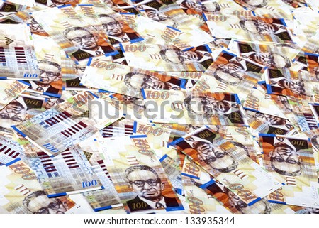 A high angle view of a very large amount of 100 NIS (New Israeli Shekel) money notes spreaded in a messy manner.