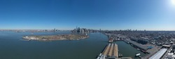 A high angle view of Governor's Island with lower Manhattan, NY in the background. Taken on a sunny day over The East River which is calm.