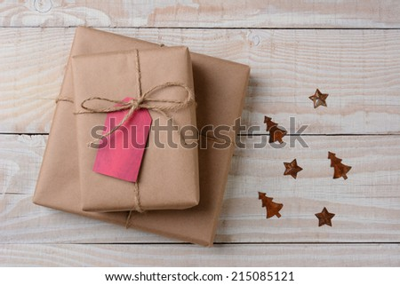 A high angle view of plain brown paper wrapped presents with red tags on a white rustic table. Small rusty metal ornaments in star and tree shapes lay by their side. Horizontal format.