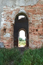 A high arched passageway on a red brick wall followed by another passageway