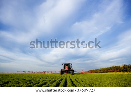 A high clearance sprayer on a field  in a prairie landscape