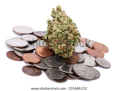 A high grade hydroponic Cannabis (Marijuana) bud resting on a pile of various USA coins - pennies, quarters, dimes, nickels. White background.