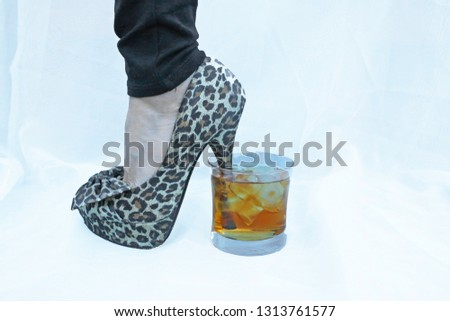A high heeled stiletto shoe is has its heel dipped in a glass of amber colored hard liquor.  #1313761577