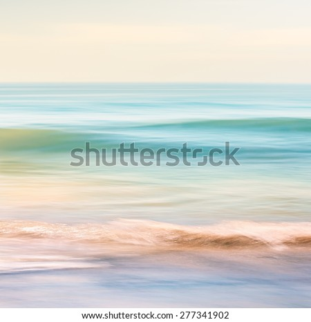 A high-key seascape featuring ocean waves with blurred panning motion.  Image displays subtle cross-processing and light, pastel colors.