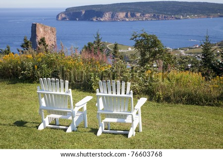 A high overlook with too Adirondack chairs considering a view of Perce Rock, the Gulf of St. Lawrence and the Gaspe.