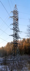 A high power line tower stands on a clearing in a winter pine forest. The wires extend from the metal support in different directions. Snow covered earth. The sun shines. Vertical panorama.