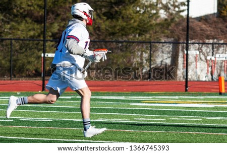 A high school boy lacrosse player is running doen the field with the ball in the net of his stick looking to make a play. Stockfoto ©