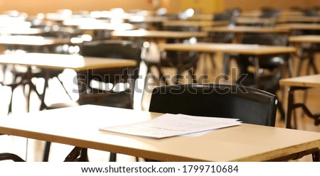 A high school hall or room set up ready for an end of year final exam to be sat by students. examination paper sitting on the edge of a desk or table.  Photo stock ©