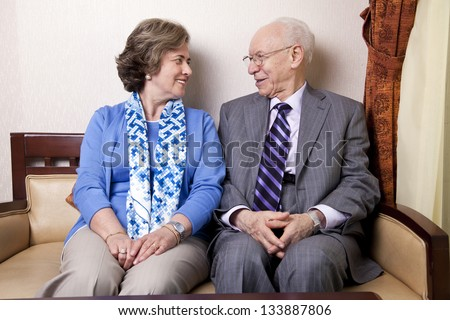 A high society senior couple (he\'s in his 80\'s, she\'s in her late 60\'s) sitting on a sofa looking at each other with very much love and joy.