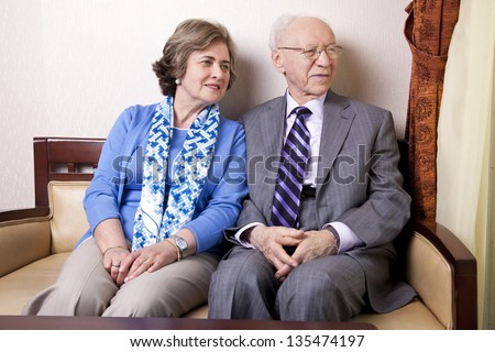 A high society senior couple (he\'s in his 80\'s, she\'s in her late 60\'s) sitting on a sofa looking away to the right side of the frame with very much love and joy.