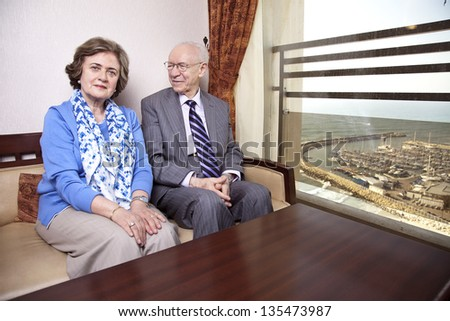 A high society senior couple (his 80\'s, her late 60\'s) sitting on a sofa. He\'s smiling and looking at her, and she\'s looking straight to the camera, with a slight smile on her face.