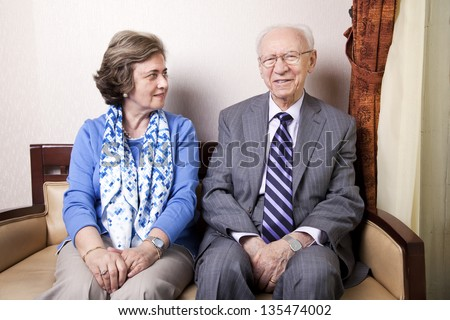 A high society senior couple (his 80\'s, her late 60\'s) sitting on a sofa. She\'s looking away to the right side of the frame, and he\'s looking straight to the camera, with a slight smile on his face.