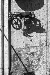 A high view angle of a motorcyle stopped on the side of a cobblestone road. black and white, natural light, high contrast & shadows