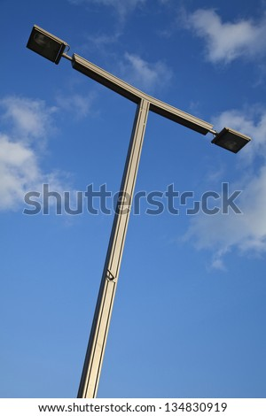 A high voltage street light shot from a low angle on the background of lovely blue sky with a few clouds. This image was shot in Tel Aviv, Israel.