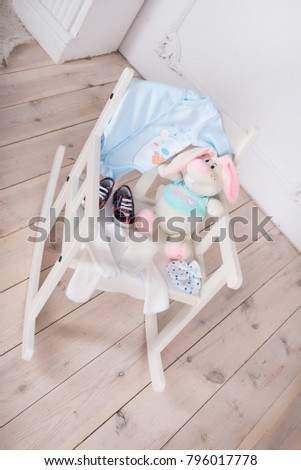 A highchair with toys and clothes for the child. Slips, body, booties #796017778