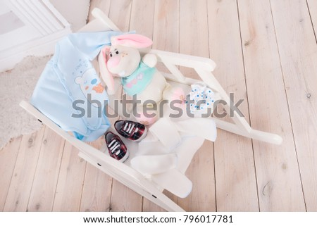 A highchair with toys and clothes for the child. Slips, body, booties #796017781