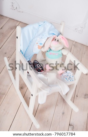 A highchair with toys and clothes for the child. Slips, body, booties #796017784